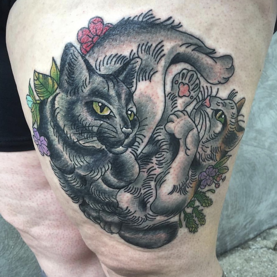 Two cats tattooed on a woman's thigh