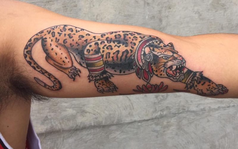 Tattoo of a colorful jaguar on an inner arm