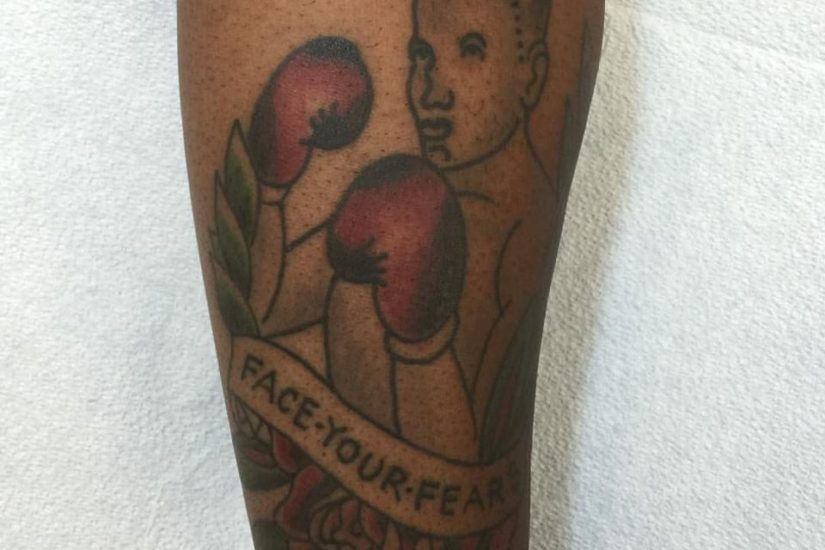 A tattoo of a fighter on an African American's left forearm